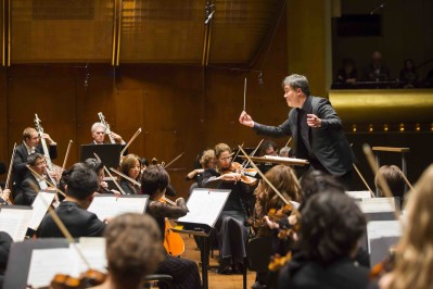This image depicts Alan Gilbert conducting the New York Philharmonic with Lisa Batiashivili as soloist at Avery Fisher Hall in 2014. Photo courtesy of Chris Lee.