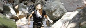 Kim Liszka navigates the large rocks along the creek bed on American Tarzan. Photo courtesy of Discovery Channel.